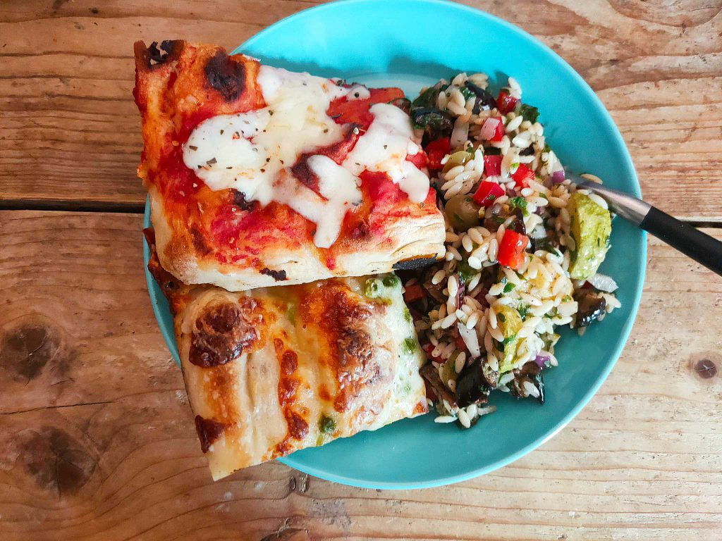 Plate with pizza slides and pasta salad